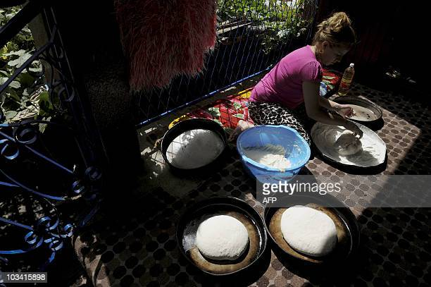 Roma woman cooks bread at her house in the town of Pec on June 19, 2010. For Roma kids expelled by Germany, Kosovo is a nightmare. They arrived in...