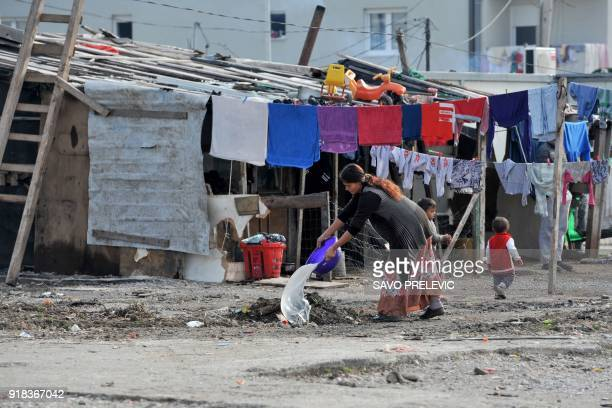 A Roma woman pours water out of a bowl outside her makeshift house in a camp in the suburb of Konik in Podgorica on February 6 2018 It was not their...