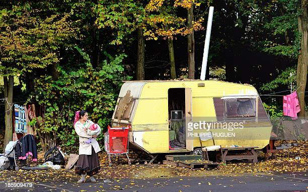 Roma women stands outside a caravan at a Roma camp in Villeneuve d'Ascq on October 25 2013 AFP PHOTO PHILIPPE HUGUEN