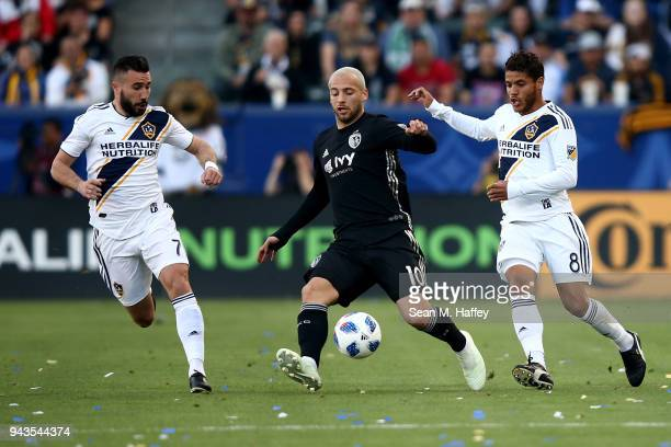 Romain Alessandrini and Jonathan dos Santos of Los Angeles Galaxy defend against Yohan Croizet of Sporting Kansas City during the first half of a...