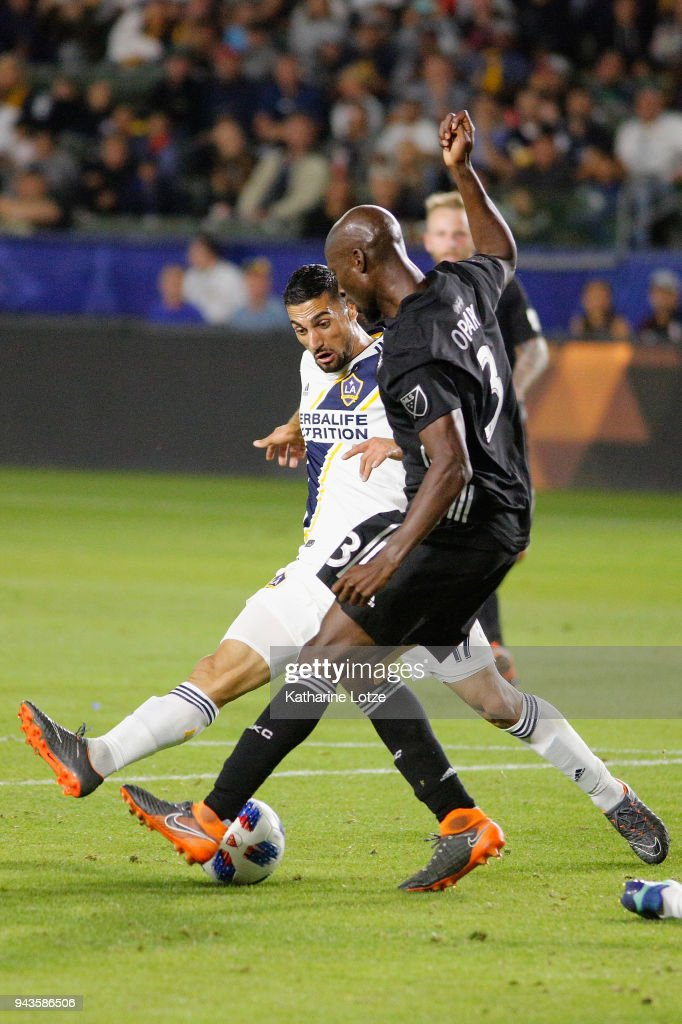 Romain Alessandrini #7 of Los Angeles Galaxy and Ike Opara #3 of Sporting Kansas City fight for control of the ball during a game at StubHub Center on April 8, 2018 in Carson, California.