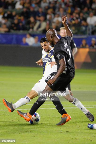 Romain Alessandrini of Los Angeles Galaxy and Ike Opara of Sporting Kansas City fight for control of the ball during a game at StubHub Center on...