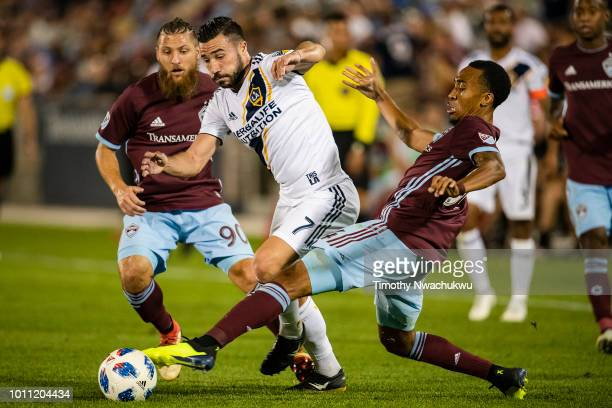 Romain Alessandrini of Los Angeles Galaxy dribbles between Marlon Hairston and Enzo Martinez of Colorado Rapids at Dick's Sporting Goods Park on...