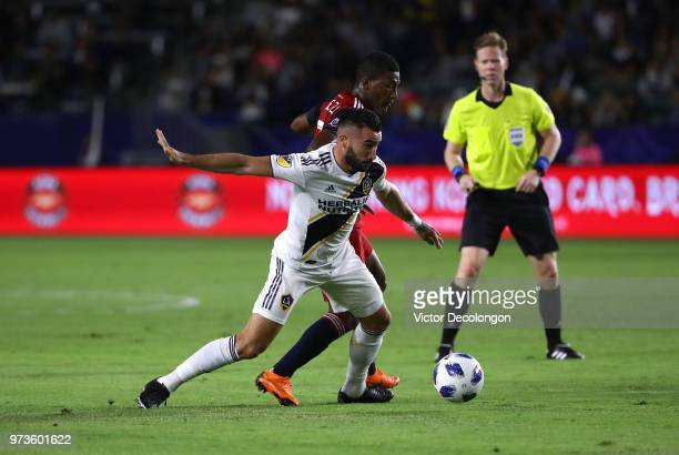 Romain Alessandrini of Los Angeles Galaxy fights for the ball with Carlos Gruezo of FC Dallas as match referee Drew Fischer looks on during the first...