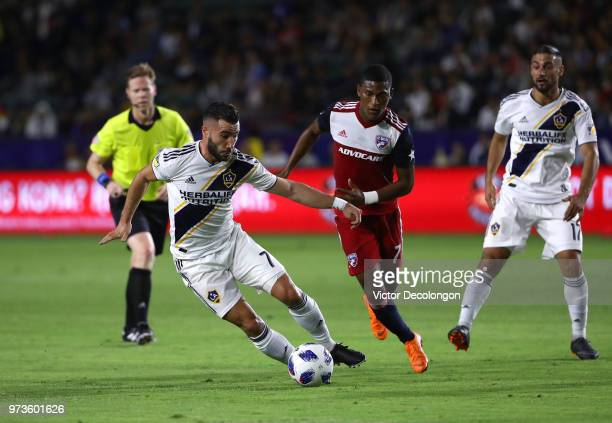 Romain Alessandrini of Los Angeles Galaxy fights for the ball with Carlos Gruezo of FC Dallas as match referee Drew Fischer and Sebastian Lletget of...