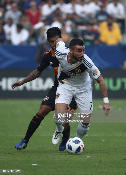 Romain Alessandrini of Los Angeles Galaxy plays the ball from A J DeLaGarza of Houston Dynamo during the first half of the MLS match at StubHub...