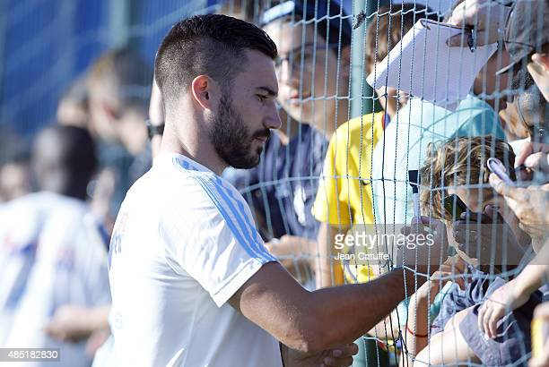 Romain Alessandrini of OM signs autographs and takes selfless with the supporters following Olympique de Marseille's training session at Robert...