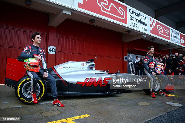 Romain Grosjean of France and Haas F1 and Esteban Gutierrez of Mexico and Haas F1 pose with the new car outside the garage during day one of F1...