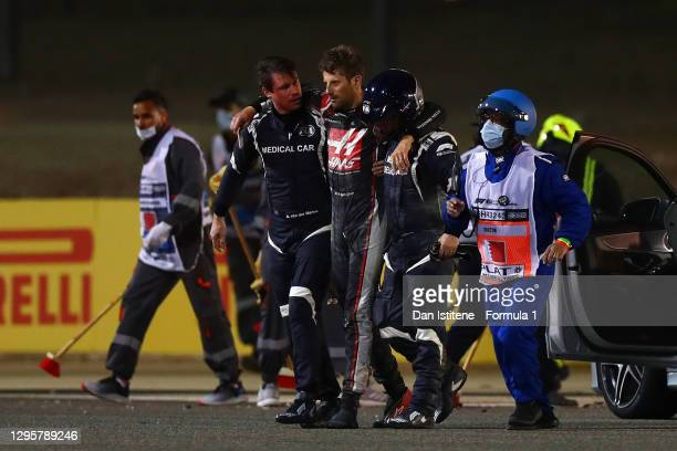 Romain Grosjean of France and Haas F1 is helped to a waiting ambulance by the FIA medical car driver Alan van der Merwe and FIA medical rescue...