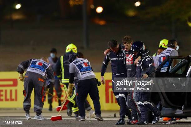 Romain Grosjean of France and Haas F1 is pictured being helped from the wreckage after a crash during the F1 Grand Prix of Bahrain at Bahrain...