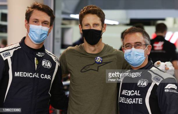 Romain Grosjean of France and Haas F1 poses for a photo with FIA doctor Dr Ian Roberts and FIA Medical Car driver Alan van der Merwe during previews...