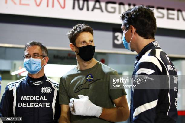 Romain Grosjean of France and Haas F1 talks with FIA Medical Car driver Alan van der Merwe and FIA doctor Dr Ian Roberts during previews ahead of the...