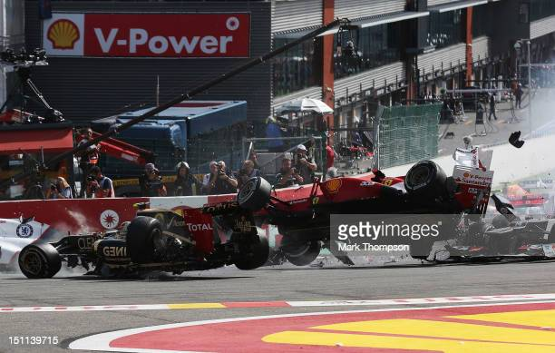 Romain Grosjean of France and Lotus and Fernando Alonso of Spain and Ferrari collide and crash out at the first corner at the start of the Belgian...