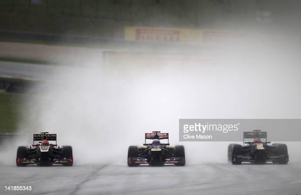 Romain Grosjean of France and Lotus, Daniel Ricciardo of Australia and Scuderia Toro Rosso and Heikki Kovalainen of Finland and Caterham drive during...