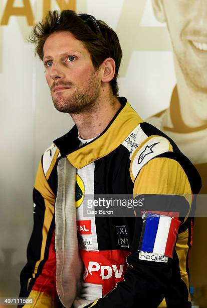 Romain Grosjean of France and Lotus wears a french national flag on his arm in tribute to the victims of the terrorist attacks in Paris as he stands...