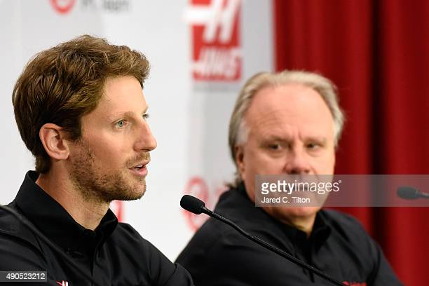 Romain Grosjean of France speaks as Gene Haas looks on during a press conference as Haas F1 Team announces Grosjean as their driver for the upcoming...