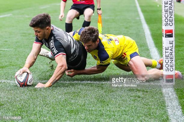 Romain Ntamack of Toulouse scores a try under pressure from Damian Penaud of Clermont during the Top 14 match between Toulouse and Clermont Ferrand...