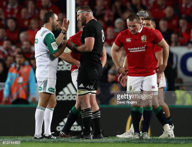 Romain Poite the referee, talks to All Black captain, Kieran Read after he reverses a decision when he orginally had awarded a penalty to the All...