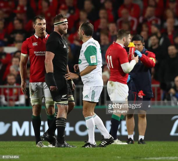 Romain Poite the referee talks to All Black captain Kieran Read and Lions captain Sam Warburton after he reverses a decision when he orginally had...