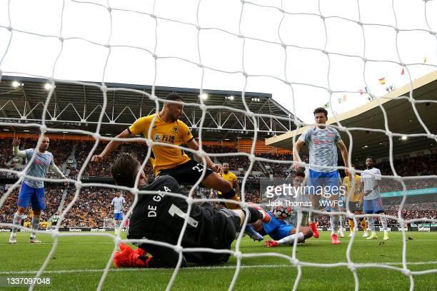 Romain Saiss of Wolverhampton Wanderers has his shot saved by David de Gea of Manchester United during the Premier League match between Wolverhampton...