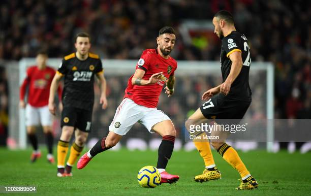 Romain Saiss of Wolverhampton Wanderers is challenged by Bruno Fernandes of Manchester United during the Premier League match between Manchester...