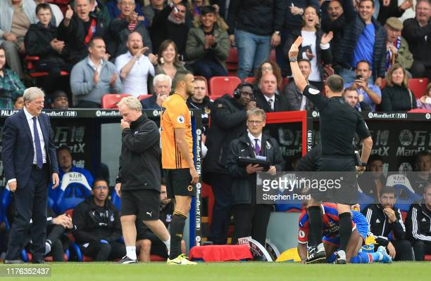 Romain Saiss of Wolverhampton Wanderers is shown a red card by referee Stuart Attwell during the Premier League match between Crystal Palace and...