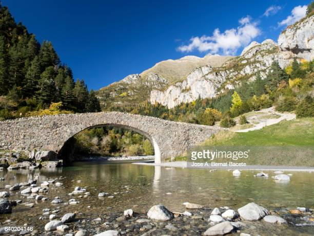 Roman ancient bridge on a great mountain river in autumn with water in motion