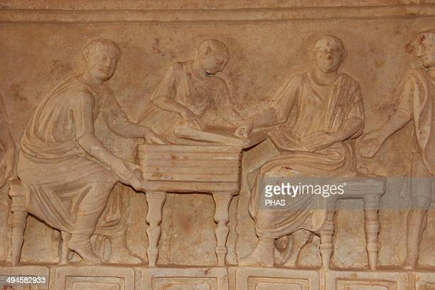 Roman art. Italy. Relief of a sarcophagus depicting a group of freedmen sitting around a table. Museum of the Baths of Diocletian. Rome.