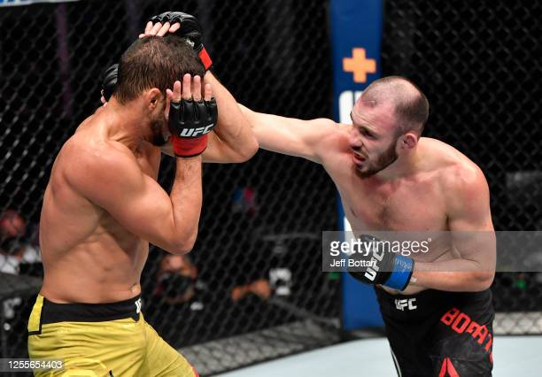 Roman Bogatov of Russia punches Leonardo Santos of Brazil in their lightweight fight during the UFC 251 event at Flash Forum on UFC Fight Island on...