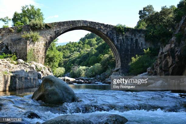 roman bridge, madrigal de la vera. - ponte ad arco foto e immagini stock
