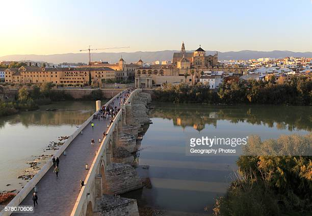 Roman bridge spanning river Rio Guadalquivir with Mezquita cathedral buildings Cordoba Spain