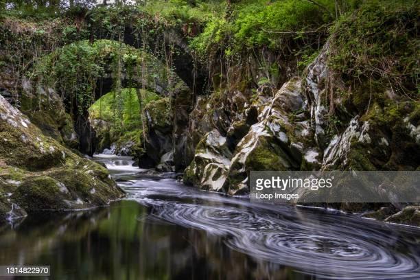 Roman Bridge twin bridges over the River Machno in summer near Penmachno in Snowdonia.