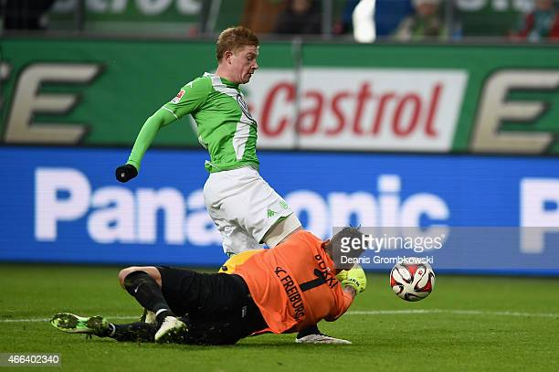 Roman Buerki of SC Freiburg takes down Kevin De Bruyne of VfL Wolfsburg during the Bundesliga match between VfL Wolfsburg and SC Freiburg at...