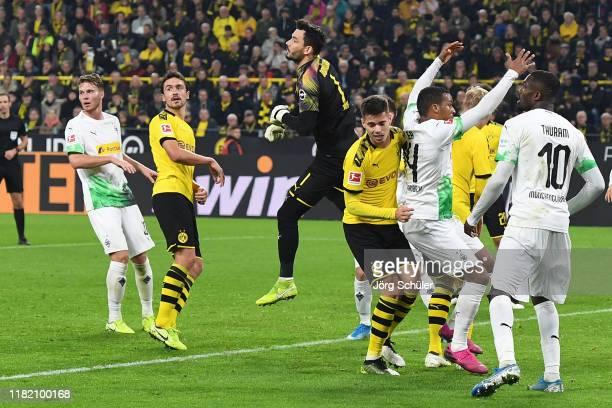 Roman Burki of Borussia Dortmund battles for possession which leads to an injury during the Bundesliga match between Borussia Dortmund and Borussia...