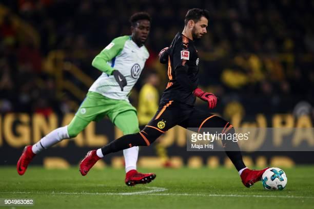 Roman Burki of Borussia Dortmund controls the ball next to Divock Origi of VfL Wolfsburg during the Bundesliga match between Borussia Dortmund and...