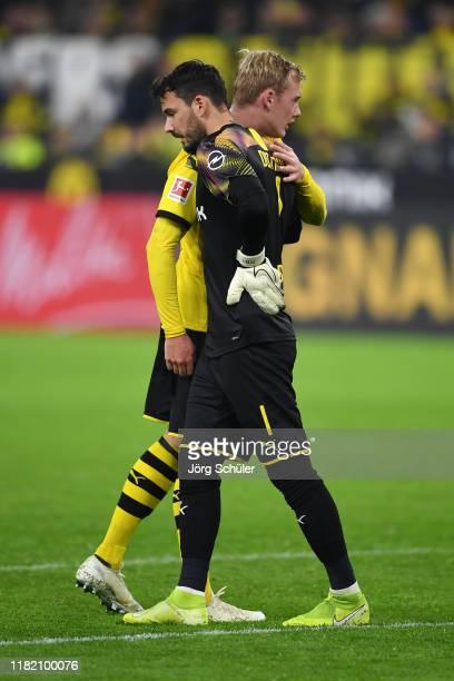 Roman Burki of Borussia Dortmund is embraced by teammate Julian Brandt during the Bundesliga match between Borussia Dortmund and Borussia...