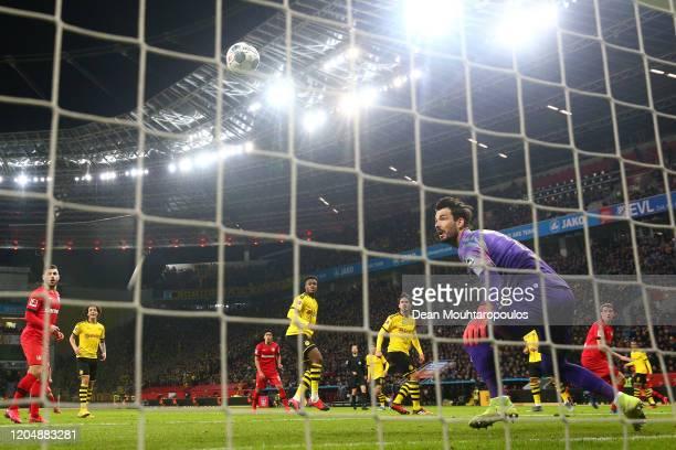 Roman Burki of Borussia Dortmund looks on as Lars Bender of Bayer 04 Leverkusen scores his team's fourth goal during the Bundesliga match between...