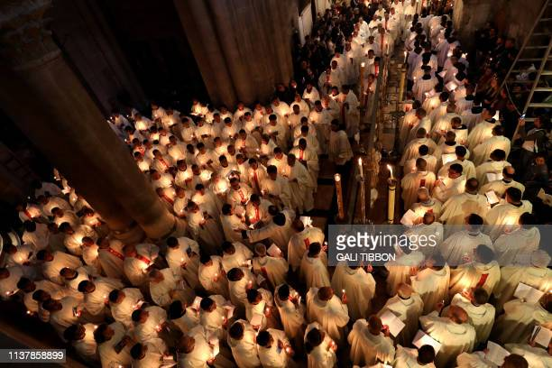 TOPSHOT Roman Catholic clergy members hold candles as they circle the Anointing stone during the Holy Thursday Easter procession at the Church of the...