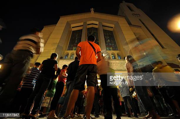 Roman Catholic devotees attend a mass in celebration of Easter Sunday outside St Domingo Church in Quezon City suburban of Manila on April 24 2011...