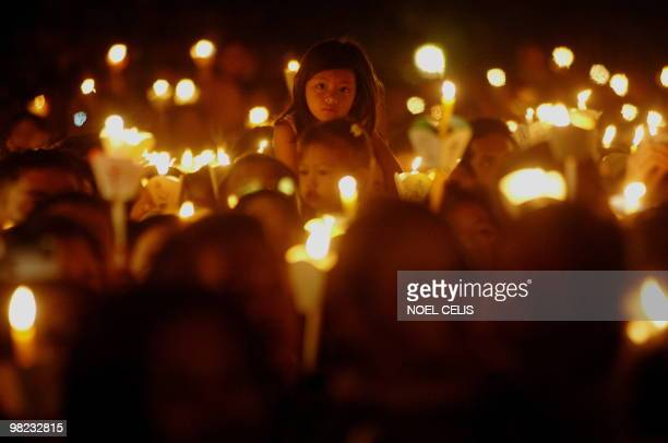 Roman Catholic devotees attend a mass in celebration of Easter Sunday outside St. Domingo Church in Quezon City, suburban of Manila on April 4, 2010....