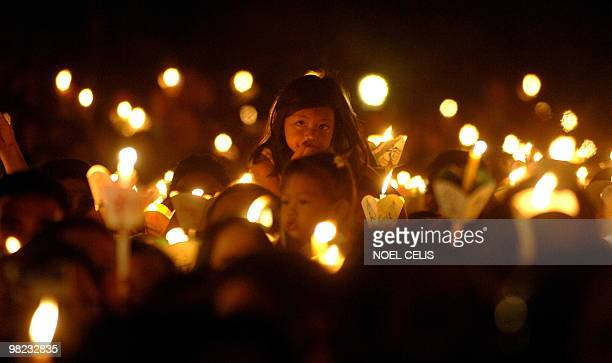 Roman Catholic devotees attend a mass in celebration of Easter Sunday outside St Domingo Church in Quezon City suburban of Manila on April 4 2010 The...