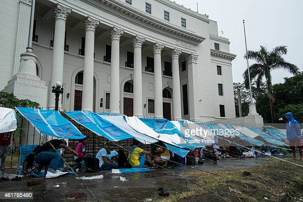 Roman Catholic devotees use sacks to make shelter from the rain while waiting for the Papal mass