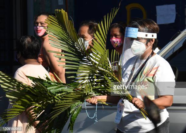 Roman Catholic faithfuls holding plant leaves wait for a priest for the blessing during Palm Sunday event in Manila on April 5 as part of the Easter...