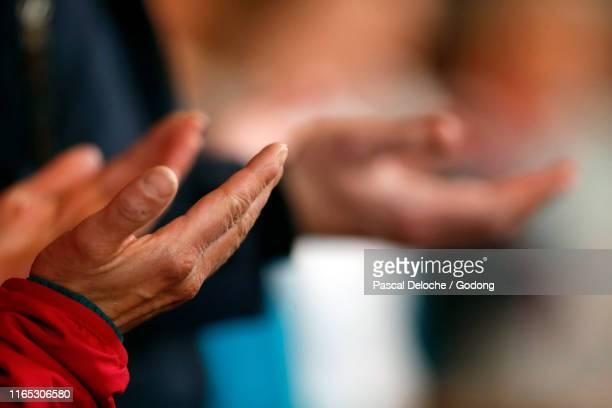 roman catholic mass.  man praying.  pater noster. saint-nicolas de veroce church. france. - katholizismus stock-fotos und bilder