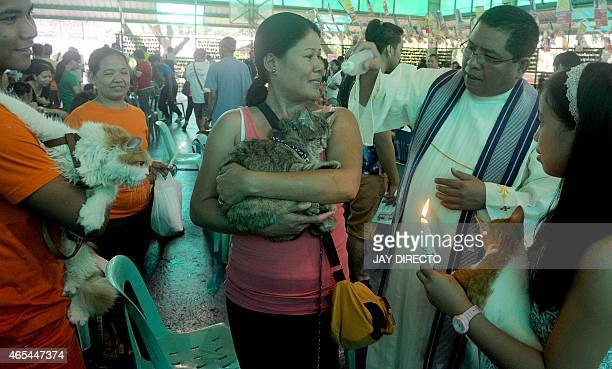 A Roman Catholic priest blesses a pet cat in suburban Manila on March 7 during a free vaccination castration and blessing of pets event The yearly...