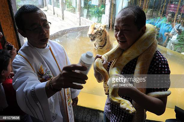 A Roman Catholic priest blesses an albino Burmese python and other animals with holy water on the eve of World Animal Day at Malabon Zoo in suburban...