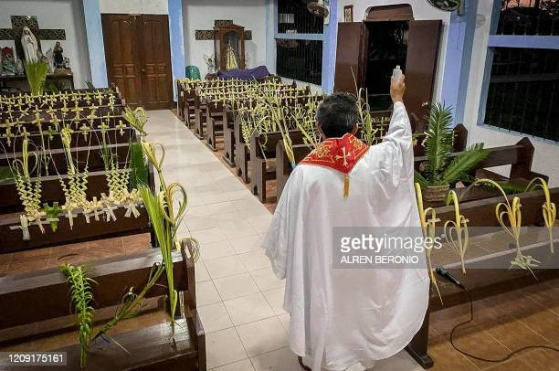 A Roman Catholic priest blesses palm branches occupying church pews during Palm Sunday event in Borongan town Eastern Samar province central...