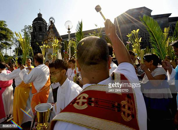 A Roman Catholic priest blesses with holy water palm during the Palm Sunday in Manila on April 5 2008 The Palm Sunday mark the start of the lenten...