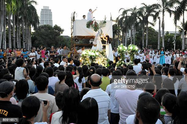 A Roman Catholic priest officiates a dawn mass in celebration of Easter Sunday outside a church in Manila on April 12 2009 The traditional 'Salubong'...