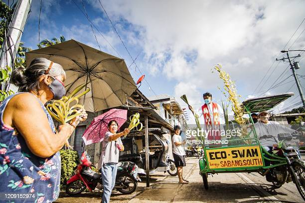 TOPSHOT Roman Catholic priest Pepe Quitorio riding on a tricycle and wearing a face mask blesses the faithfuls holding coconut leaves during Palm...